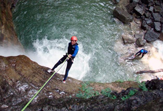 Toboganes, saltos y pozas te esperan en los barrancos. En la imagen, un barranquista rapelando una pared